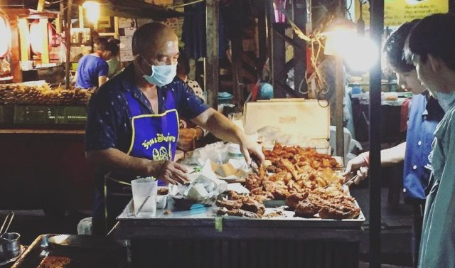 Thai man serving fried chicken