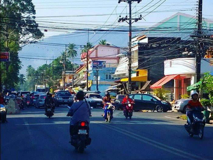 motorbikes driving down the road in a Thai town