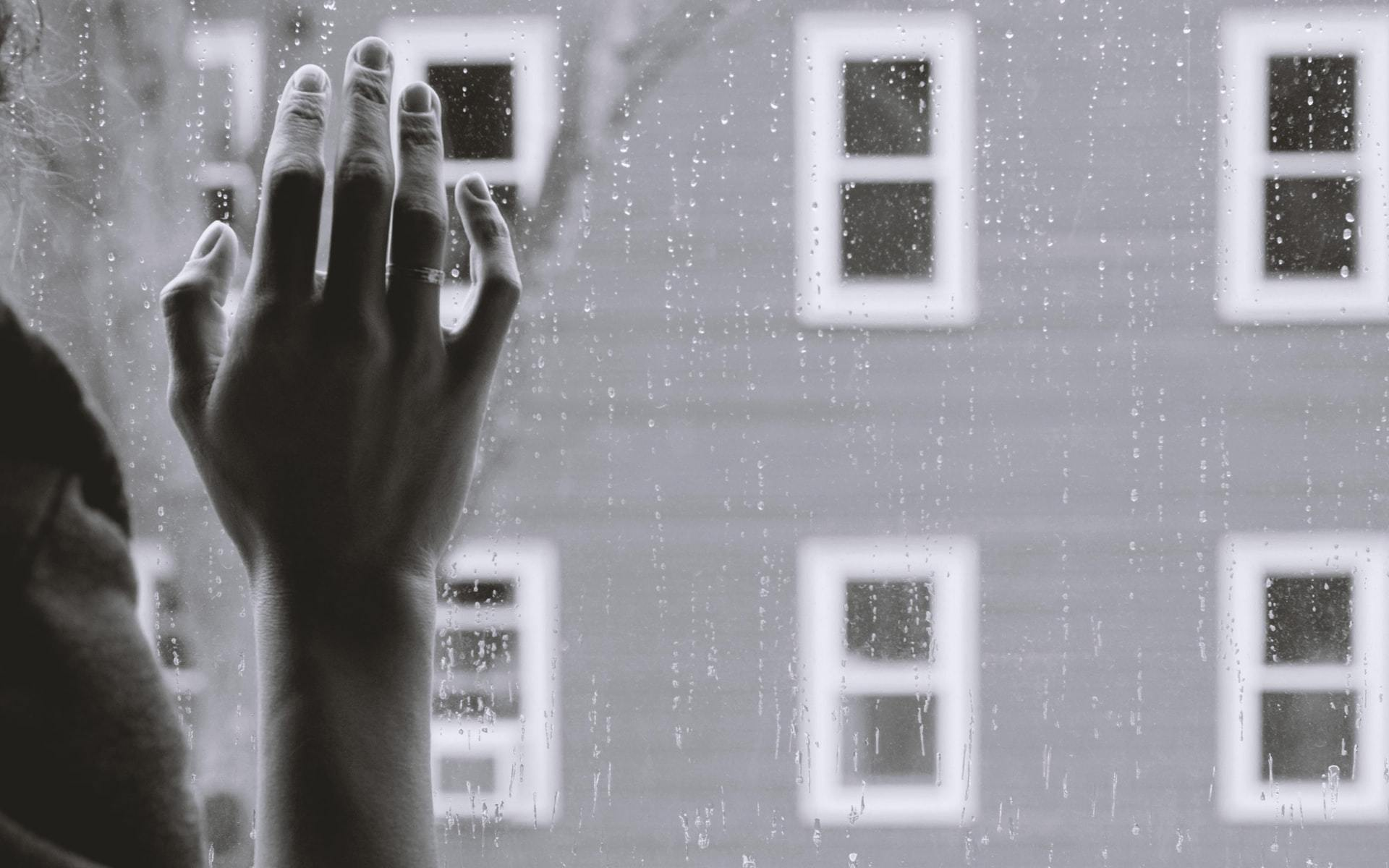 woman's hand against a window with rain outside